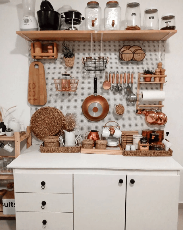 a small kitchen organized with a pegboard for vertical storage and an open shelf is a very smart idea for a studio apartment