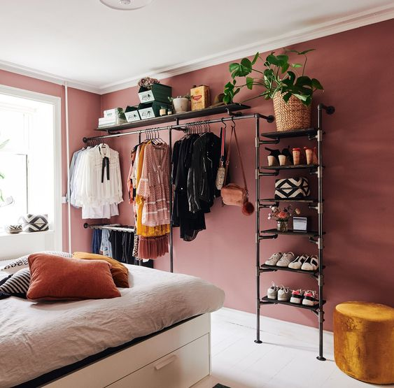 a cool makeshift closet made with a large metal piping unit looks airy and stylish and adds to the bedroom style