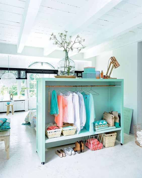 a turquoise open storage unit used as a closet doubles as a bed headboard and ads color to the studio