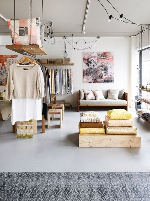 a makeshift closet looks airy and separates the parts of this studio apartment, which is a great idea