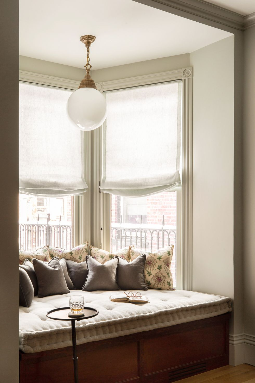 a bay windowsill turned into a comfortable seating for reading or having meals plus additional storage inside