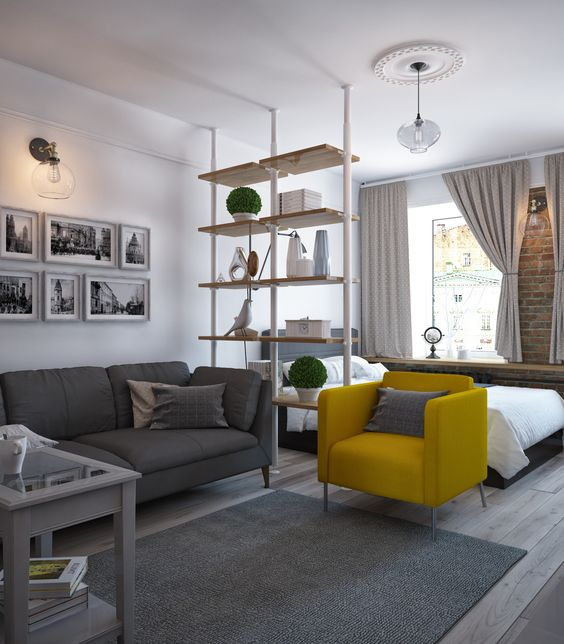 a neutral studio apartment accented with a single yellow chair looks very stylish and elegant