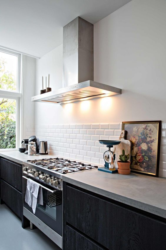 a Nordic black kitchen with sleek cabients, concrete countertops, a white tile backsplash and stainless steel appliances