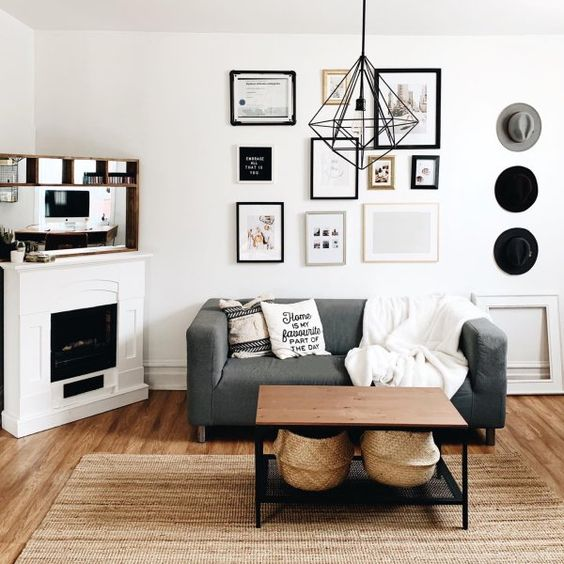 a Scandi boho living room with a small non-working fireplace, a grey loveseat, a table, a gallery wall and some hats on display