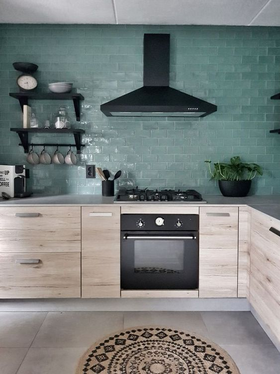 a Scandinavian kitchen with green tile walls, light stained cabinets, black fixtures and shelves and a boho rug