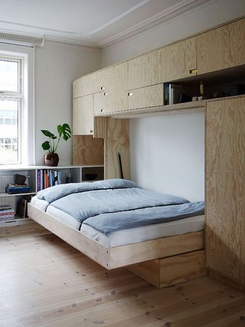a Scandinavian room with a large blonde plywood storage unit and a Murphy bed that can be hidden anytime