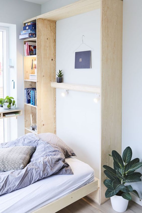 a Scandinavian room with a storage unit of blonde wood and a Murphy bed is a very serene and airy space