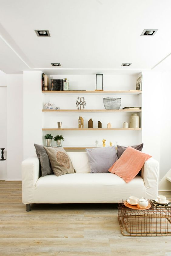 a Scandinvian living room done in neutrals, with a loveseat, built-in shelves and bright pillows is a chic space