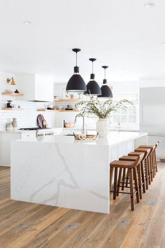 a beautiful all-white kitchen with a large kitchen island and a waterfall countertop, chic black pendant lamps and wooden stools