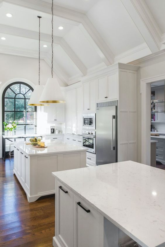 a beautiful all-white ktichen with two kitchen islands and white quartz countertops plus white and gold pendant lamps and black fixtures
