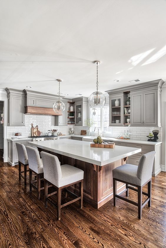 a beautiful and airy farmhouse kitchen with grey cabinetry, a wooden kitchen island and hood, white quartz countertops and comfy stools