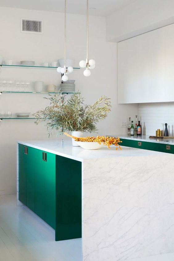 a beautiful emerald and white kitchen with a white tile backsplash and a gorgeous white stone waterfall countertop plus chic pendant lamps