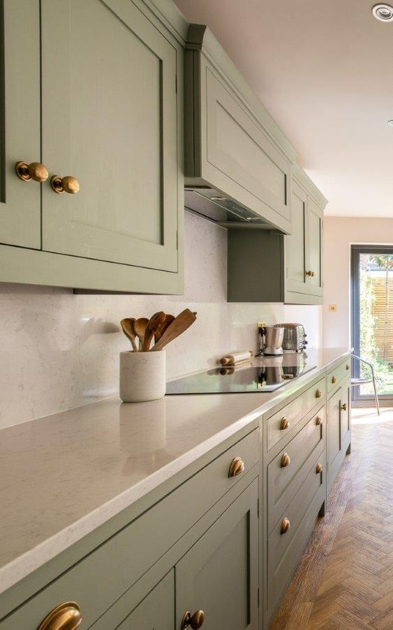 a beautiful light and airy green kitchen featuring quartz worktops and brass knobs and cup pull handles is chic and elegant