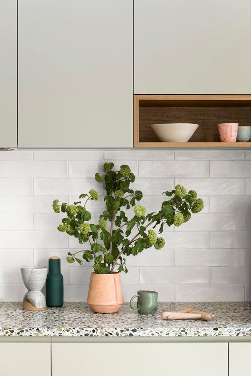 a beautiful light green kitchen with sleek cabinets, white skinny tiles and a bold terrazzo countertop that adds spice to the space