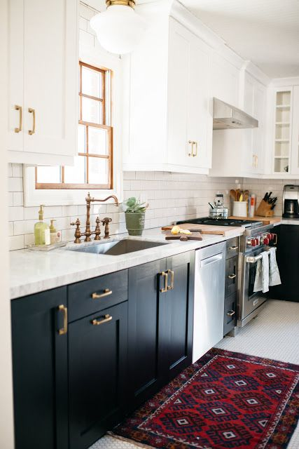 a beautiful two tone kitchen with white and black cabinets, a white tile backsplash and white quartz countertops and brass handles