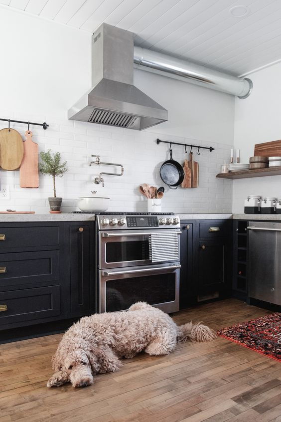 a black farmhouse kitchen with a concrete countertop, a white tile backsplash and stainless steel appliances
