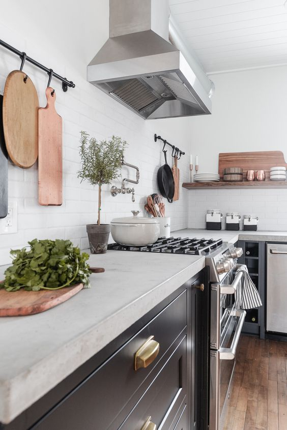 a black farmhouse kitchen with concrete countertops and a white til backsplash plus stained wooden shelves