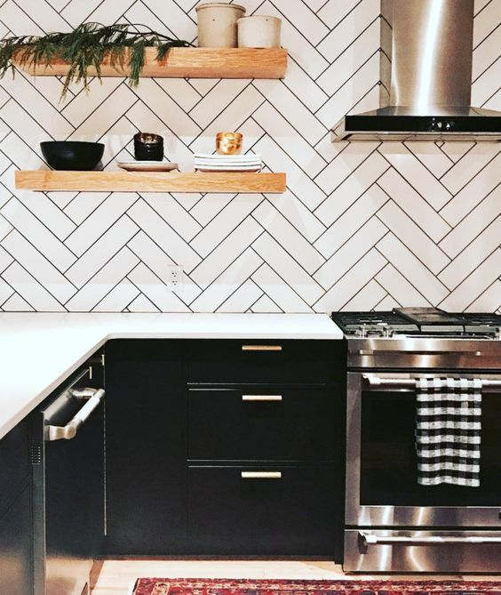 a black farmhouse kitchen with white countertops, a herringbone backsplash with black grout and floating shelves