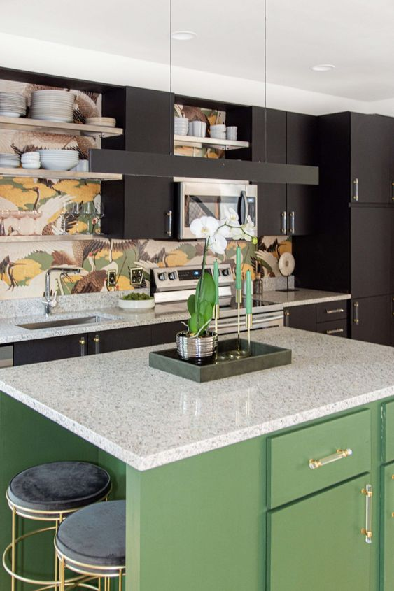 a black kitchen with a green kitchen island and black and white terrazzo countertops plus a bold backsplash