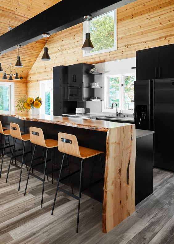 a black kitchen with a matching kitchen island and a raised live edge wooden waterfall countertop to create a contrasting look