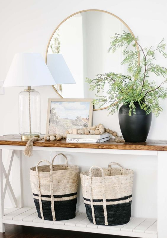 a black vase with greenery branches creates a strong spring feel in the space and makes it welcoming and lively