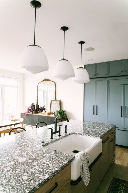 a blonde wood kitchen island with a black terrazzo countertop and black handles look chic and stylish