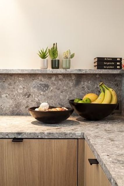 a blonde wood kitchen with a grey terrazzo countertop and backsplash plus a long shelf instead of upper cabinetry