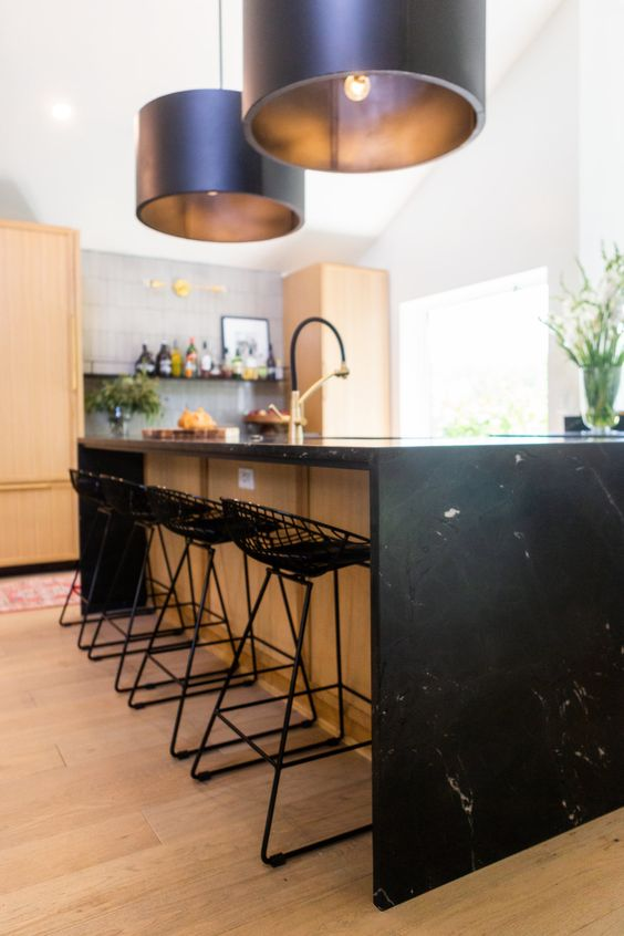 a blonde wood kitchen with a large kitchen island and a black stoen waterfall countertop plus black stools and lamps