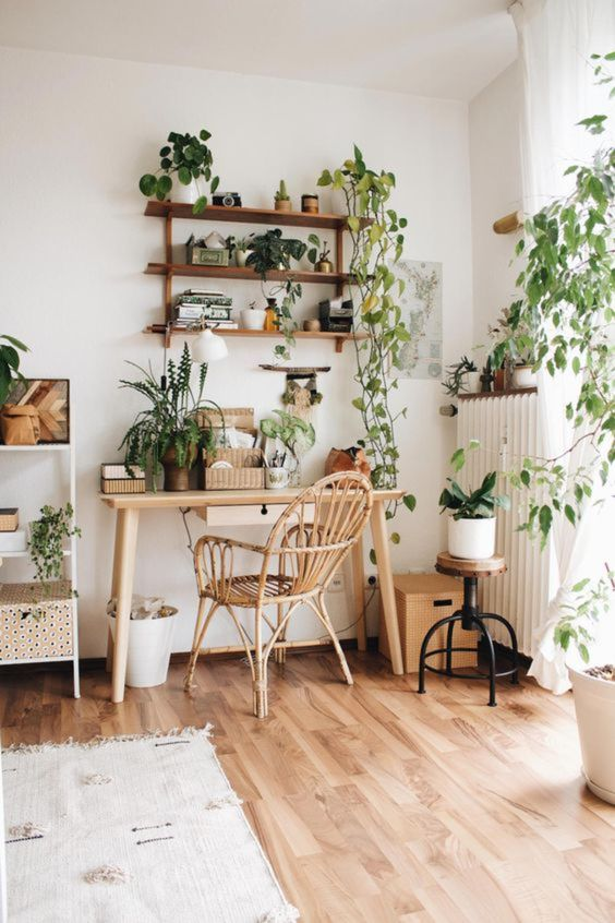 a boho home office done in neutrals and with much potted greenery including cimbing plants for a calming feel