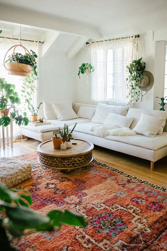 a boho living room with a neutral sectional plus a bold rug, climbing plants and a fluffy ottoman