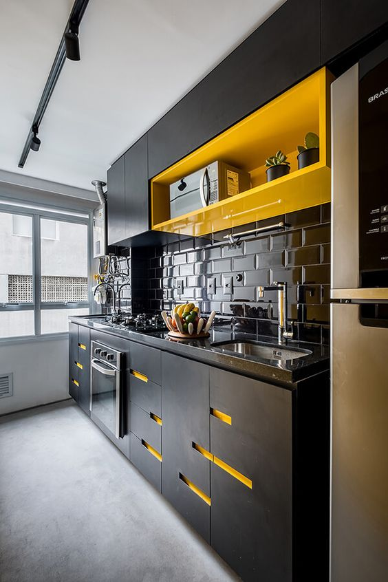 a bold and super modern black and yellow kitchen with a glossy black subway tile backsplash and bold neon yellow touches