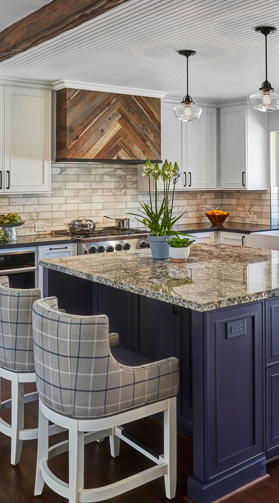 a bold kitchen with white cabinets, a navy kitchen island, a marble tile backsplash and grenite countertops plus plaid stools