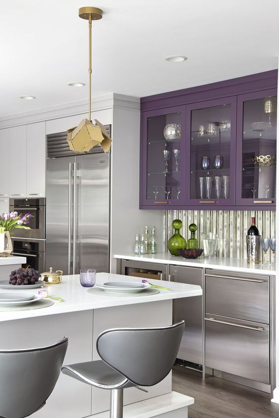 a bold silver and purple kitchen, a white kitchen island, grey stools, a faceted pendant lamp and a shiny backsplash