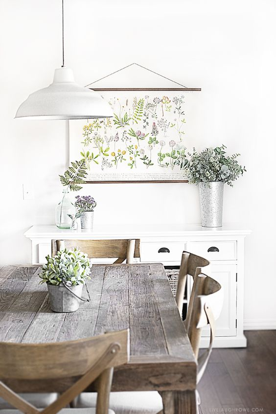a botanical poster, a tall bucket with eucalyptus, vases and buckets with blooms and ferns for rustic decor