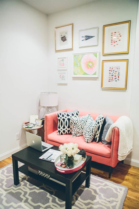 a bright and cool nook with a pink loveseat, a coffee table, a pretty and bright gallery wlal is a cozy space
