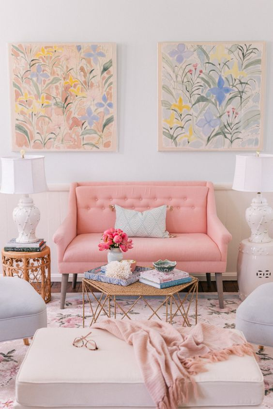 a bright and glam living room with a pink loeseat, ottomans, gilded tables, pretty floral watercolors on the wall