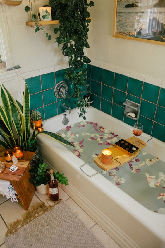 a bright bathroom with emerald tiles, some potted plants and a climbing one to create an urban jungle feel