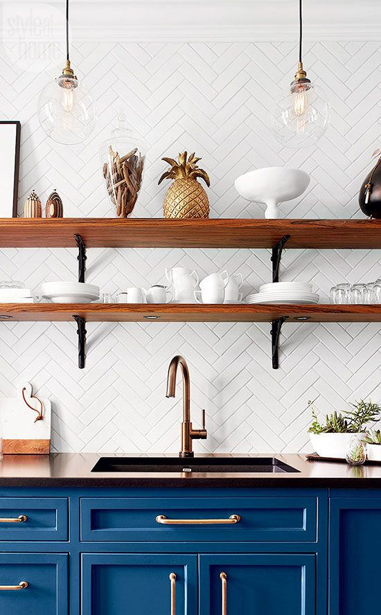 a bright blue kitchen in vintage style, with dark coutnertops, wall mounted shelves and a lovely white herrignbone backsplash