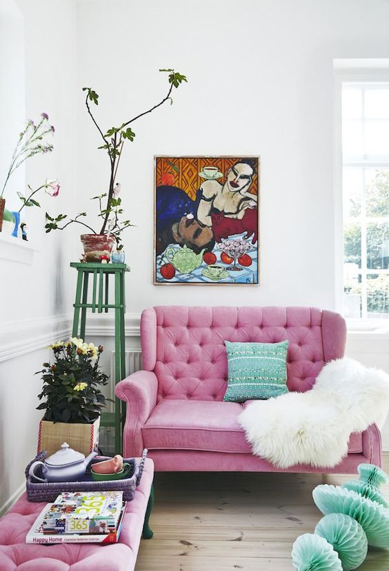 a bright nook with a pink loveseat and a matching ottoman, a green pillow, a bold artwork, potted plants and blooms
