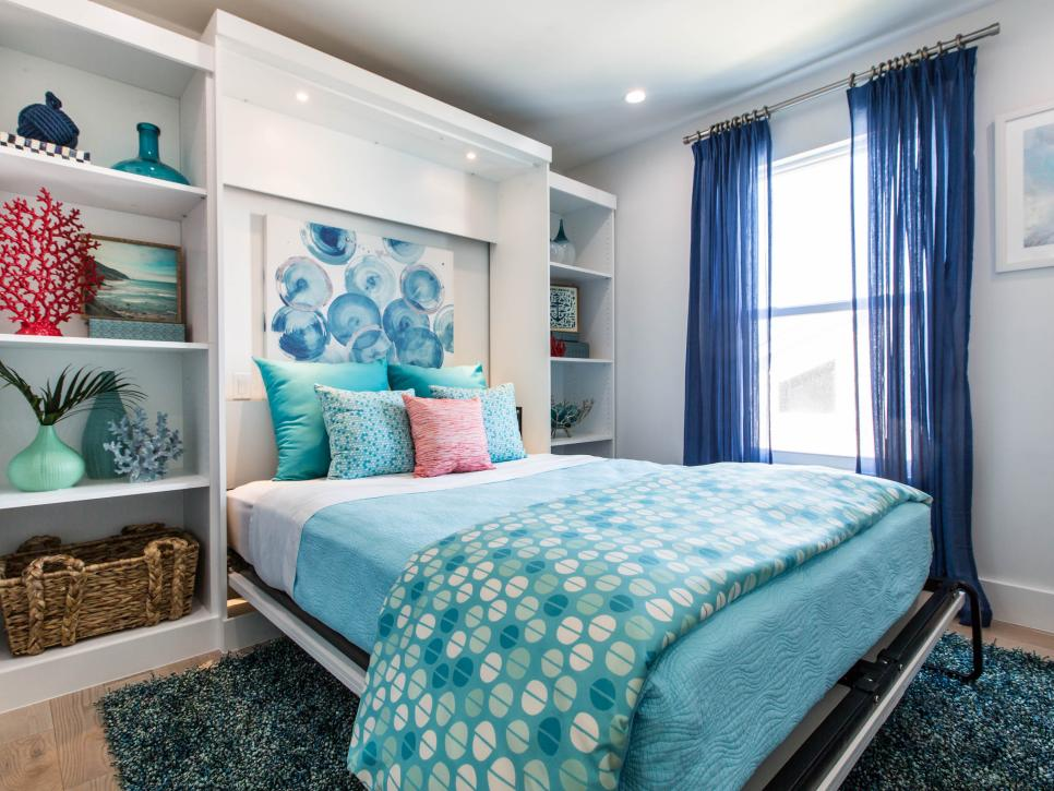 a bright room with a built in white storage unit, with a Murphy bed and bright textiles for a coastal feel