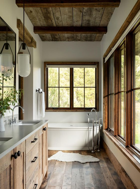 a cabin bathroom with a reclaimed wood ceiling and floor, windows in wooden frames and a large vanity