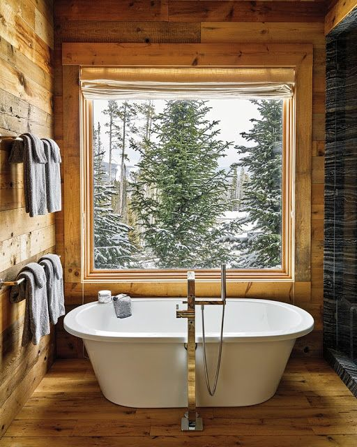 a chalet bathroom fully clad with wood and with a dark stone shower space is pure luxury, and the view is cool
