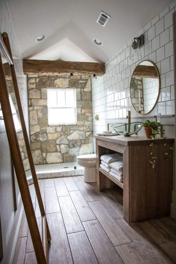 a chalet bathroom with a stone wall, a wooden floor and a wooden vanity, a couple of mirrors and a wooden beam