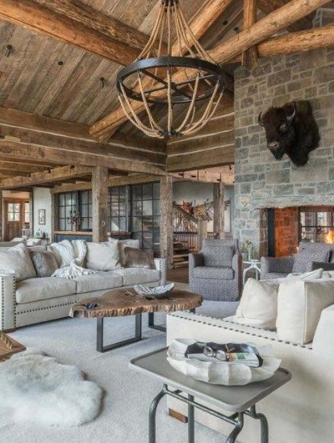 a chalet living room with a stone fireplace, neutral furniture, a chandelier of wooden beads and a metal table