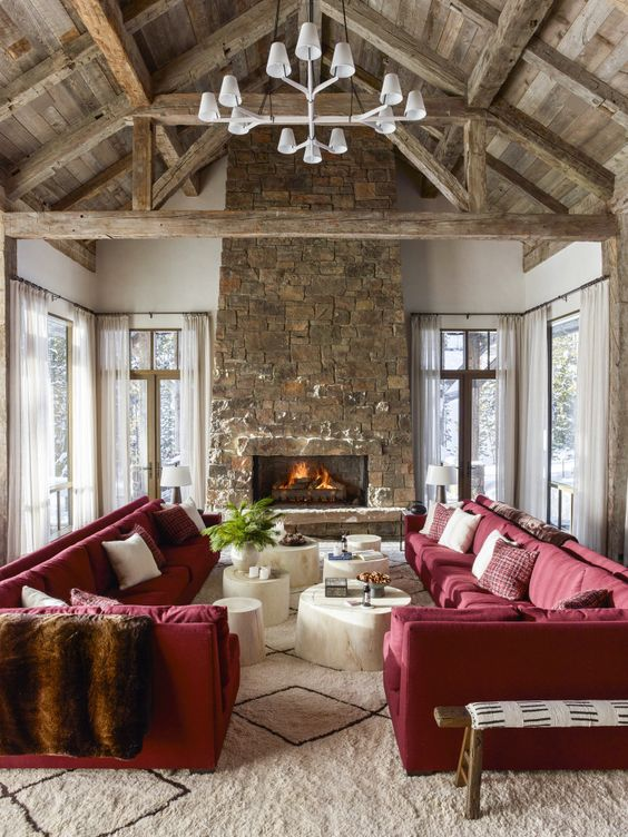 a chalet living room with a wooden ceiling with beams, a stone fireplace, red sofas and whitewashed coffee tables