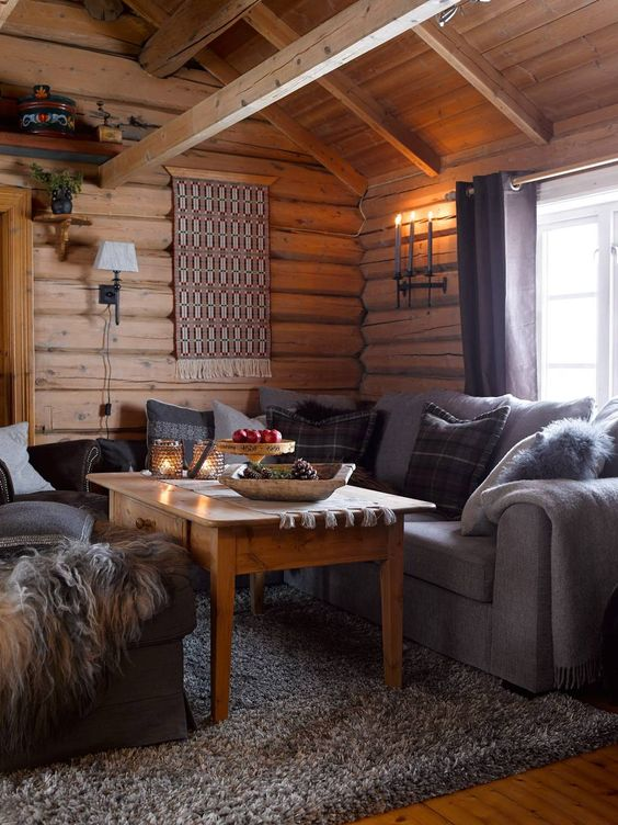 a chalet living room with wooden walls and a ceiling, grey sofas, a boho hanging on the wall and a wooden table