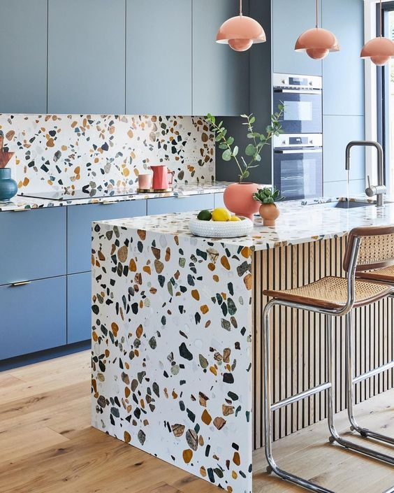 a cheerful kitchen with blue sleek cabinets and bright terrazzo countertops and a backsplash plus coral pendant lamps