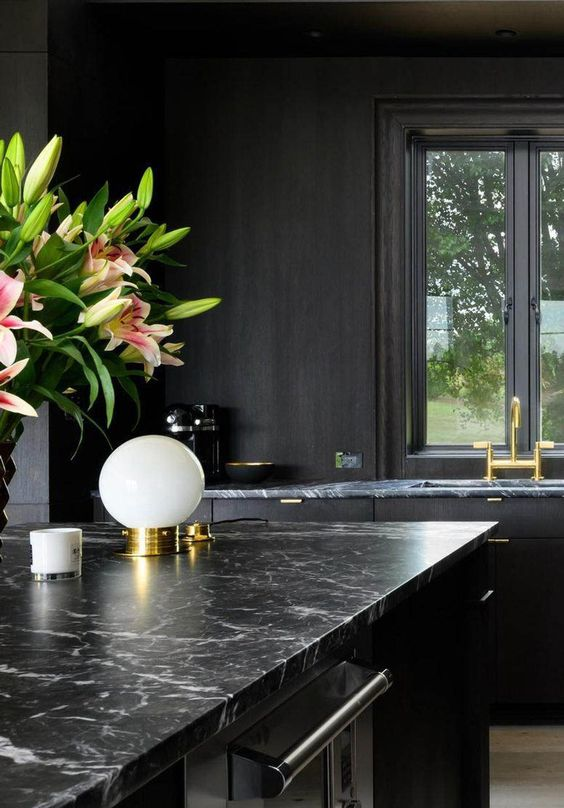 a chic black kitchen with black granite countertops, gold fixtures and touches for a super elegant and refined look