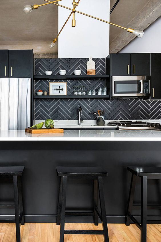 a chic black kitchen with white countertops, a black herringbone backsplash and an elegant gilded chandelier is elegant and refined