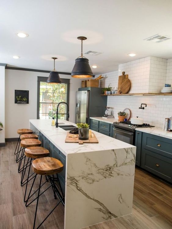 a chic blue farmhouse kitchen with white stone countertops and a matching kitchen island with a waterfall countertop is very cool